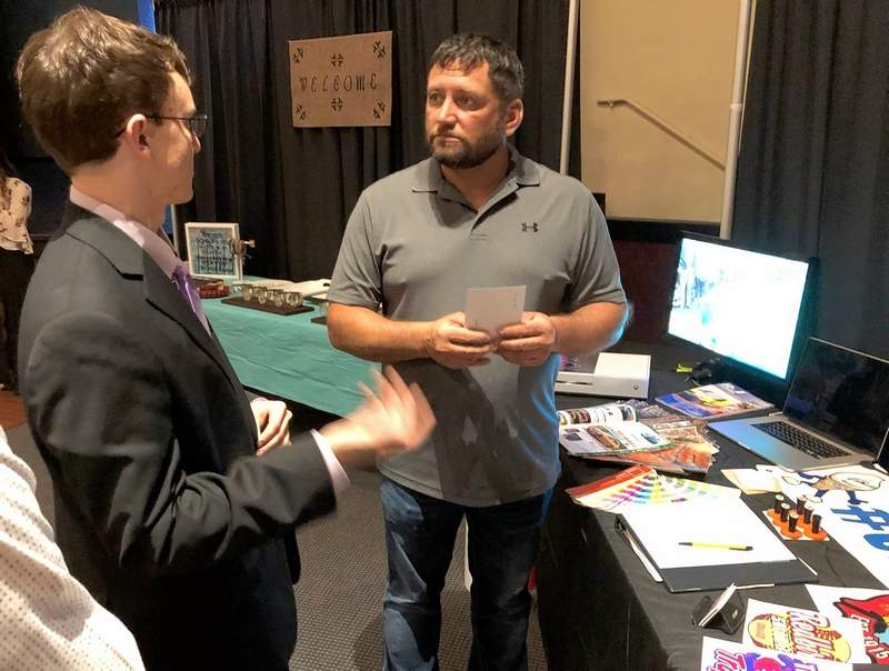 Benton Consolidated High School senior Carson Webb, left, discusses his product offerings with a potential customer during last week's EDGE trade show at the Benton Civic Center.