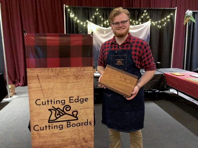 Isiah Edgell shows one of his creations during the Franklin County EDGE trade show last week. Edgell, a senior at West Frankfort High School, owns 'Cutting Edge Cutting Boards.'