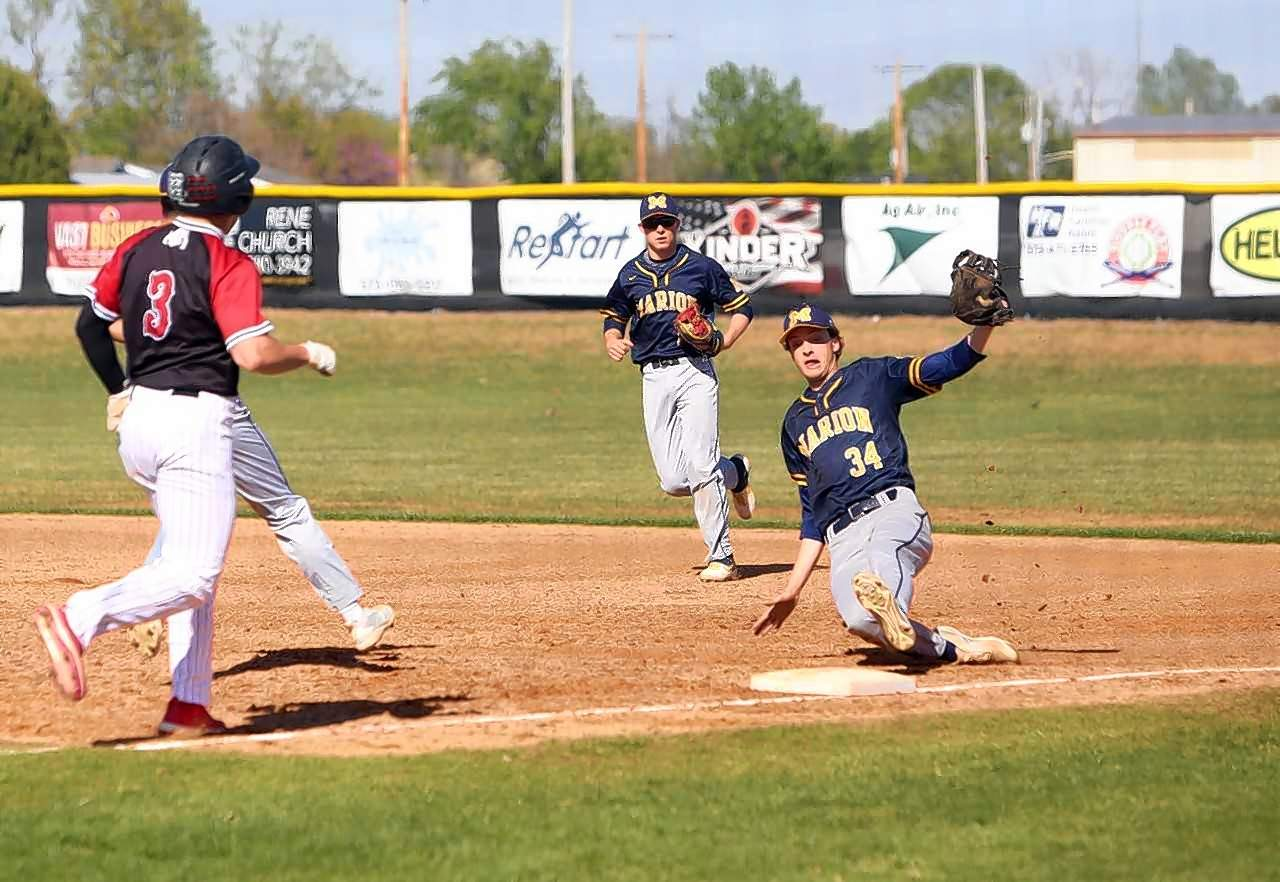 Marion's Mitchell Jackson slides to make a putout at first base in the second inning.