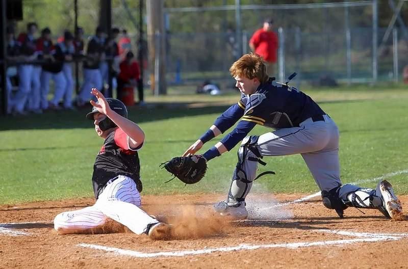 Sikeston's Nate Self slides around Marion catcher Ryan Trokey to score on a fielder's choice in the third inning.