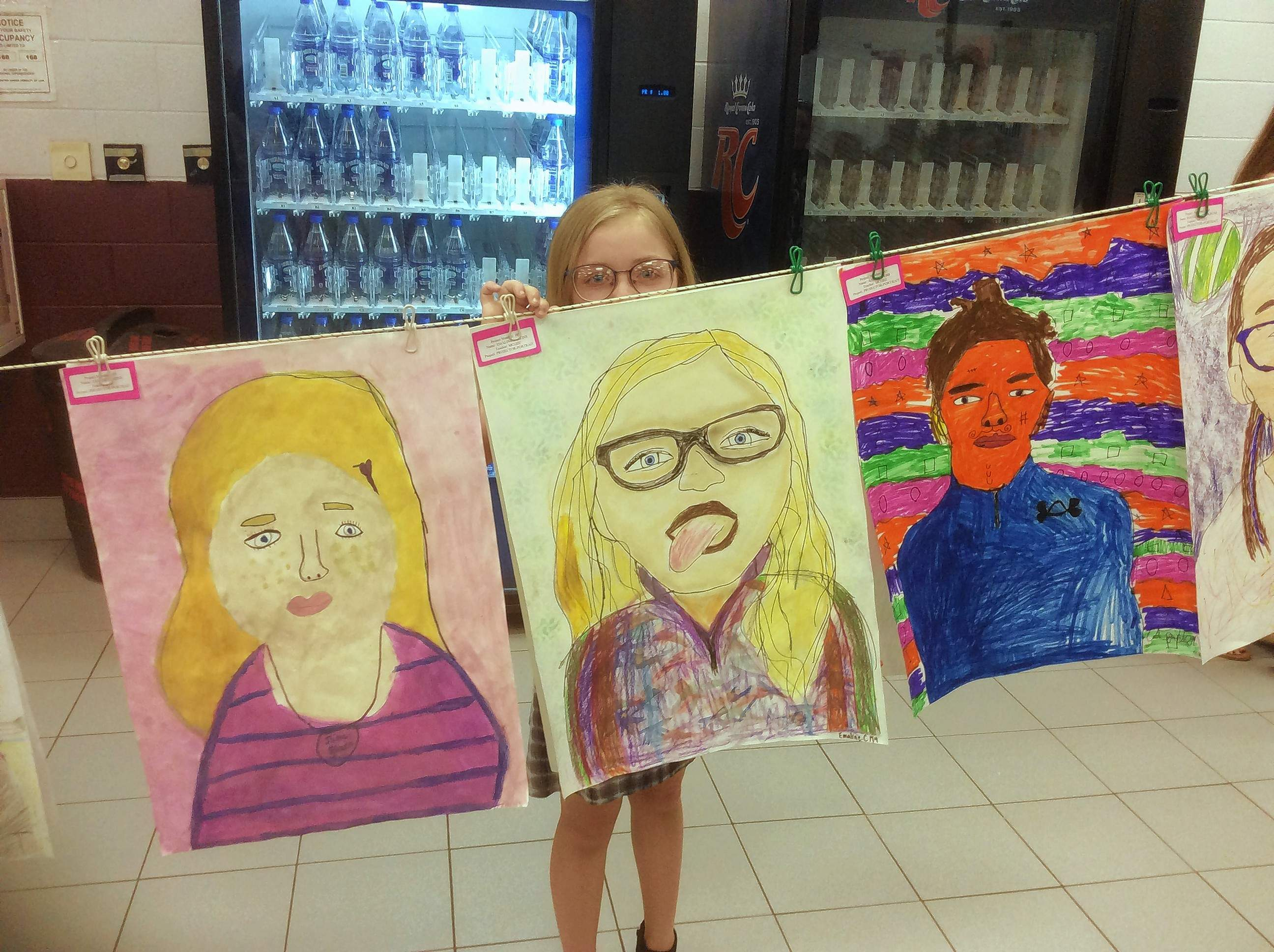Fourth-grader Emaline Collins peeks over her large-scale self-portrait at the K-8 Art Show April 23 in the Benton Middle School Gym and Commons.