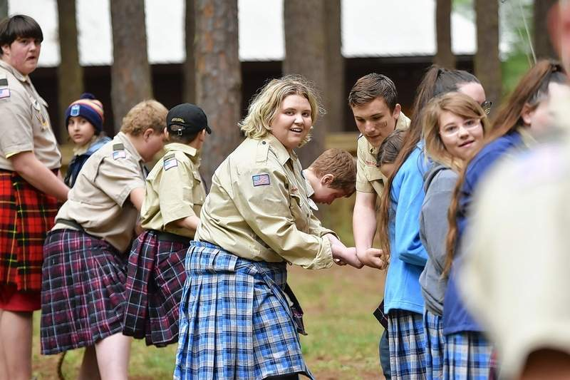 Madeleine DeNeal of Harrisburg, a member of Scouts BSA Troop 156G of Christopher, competes in the tug-o-war during the Spring Camporee Highland Games at Pine Ridge Scout Camp near Makanda. Below, Logan Grathler of Harrisburg Troop 23 competes in hammer toss.