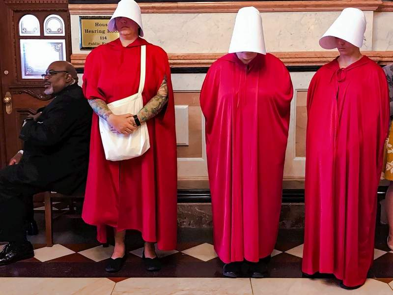 """Women dressed as Handmaids, characters from Margaret Atwood's dystopian novel, """"The Handmaid's Tale,"""" stand by as House Democrats meet on the other side of the door to discuss the future of the Reproductive Health Act on May 22 at the Capitol in Springfield."""