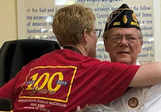 A tearful John Metzger, right, gets a hug from Maureen Sanders following a standing ovation Metzger received in honor of his service. After 22 years of giving in one form or another, Metzger is stepping away from his official duties at the Benton American Legion. See more photos on page 10.