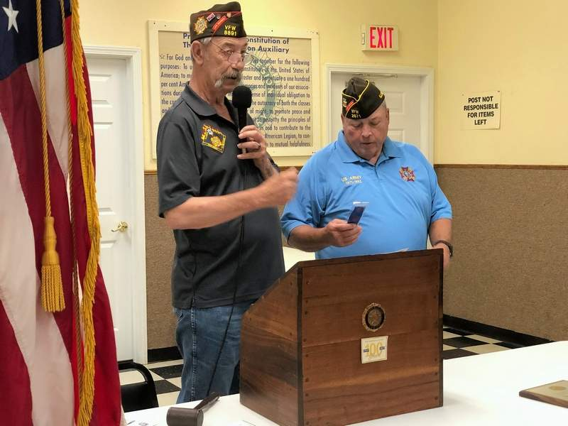 Commander Clarence Caraker of the VFW 15th District presents Gary Gravel with a ribbon for the district colors to display with the flag. The ribbon signifies the Benton post's achievement of 100 percent membership, a feat not easily achieved.