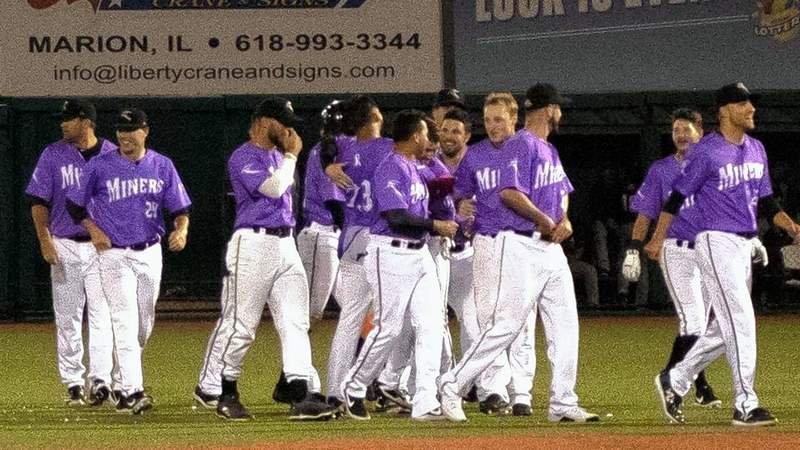 The Southern Illinois Miners, dressed in purple jerseys Friday in recogntion of cancer survivors, celebrate a walkoff double by Arturo Nieto.