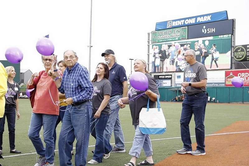 Carl and Brenda Teaney of Du Quoin look at the camera while walking onto the field at Rent One Park Friday.