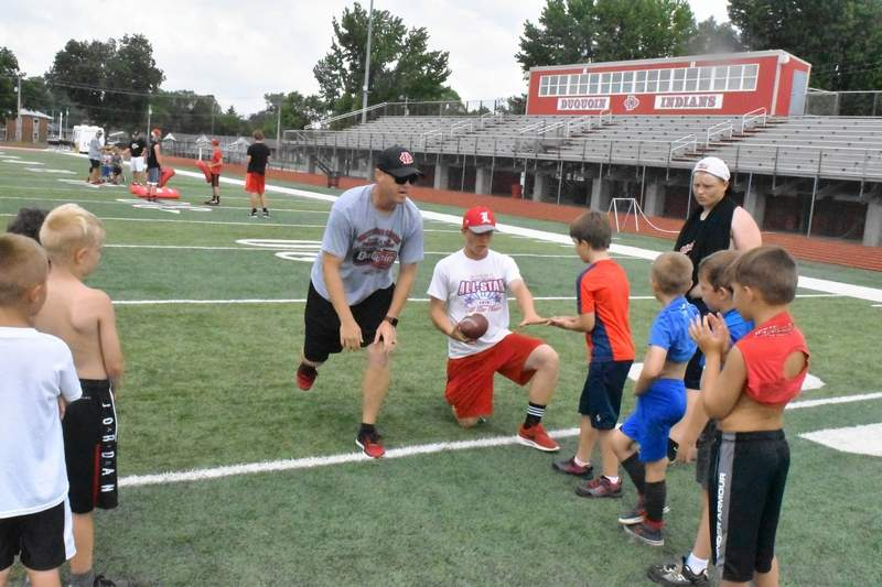 DHS Indians head coach Derek Beard chats with campers while Alex Zimmerman demonstrates the proper technique in fielding a snap from center as the quarterback.
