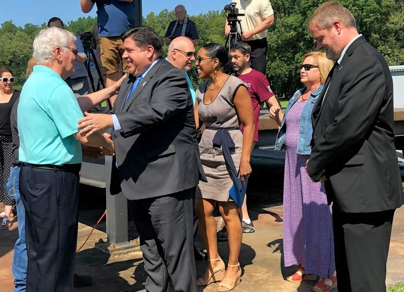 Former U.S. congressman Glenn Poshard, left, greets Gov. J.B. Pritzker as Walker's Bluff owner Cynde Bunch and Sesser Mayor Jason Ashmore look on.