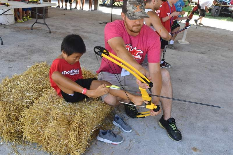Thad Longmire, 9, of Iowa, was quite skilled shooting arrows with his feet with a little help from archery instructor Seth Flint of Du Quoin.