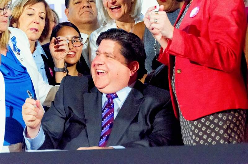 Gov. J.B. Pritzker laughs while signing into law the Reproductive Health Act during a ceremony June 12 at the Chicago Cultural Center. The governor last week signed more than 30 new laws, putting the total number of bills signed from the past legislative session at more than 100.