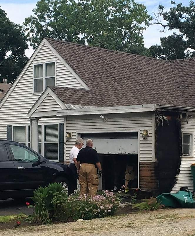Richard J. Wennerberg Jr. is being called a hero by one of his neighbors after alerting an elderly neighbor of a garage fire, then helping put out the flames with a hose.