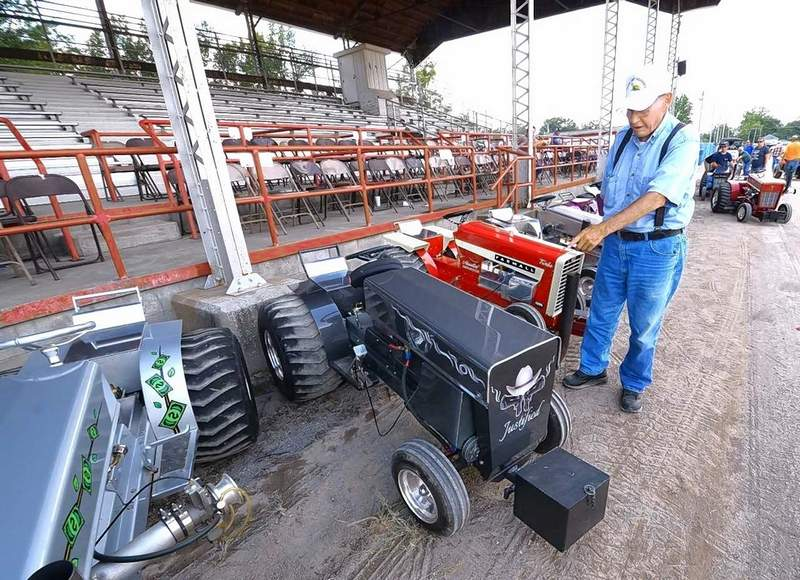 Carl Frueh of Greenville points something out to a friend about one of the custom-built, high-powered garden tractors at the 163rd Williamson County Fair Friday in Marion. The lifelong farmer said he's been tinkering with souped-up tractors for over 60 years.