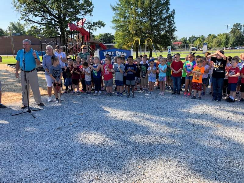 Flanked by his granddaughter, Ella, and her Jefferson School classmates, Jimmy Dean speaks at the dedication of the Johnston City park that will bear the name of his son.