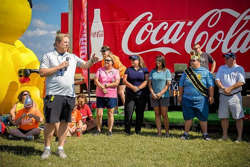 Top: With an assist from Master of Ceremonies Keenan Rice, John Henley and Brenna Asbury lead the Special Olympics Athlete Oath.Bottom: Du Quoin State Fair Manager Josh Gross addresses the crowd at the annual Southern Illinois Special Olympics Duck Derby Dash Sunday. State Rep. Terri Bryant is also pictured.