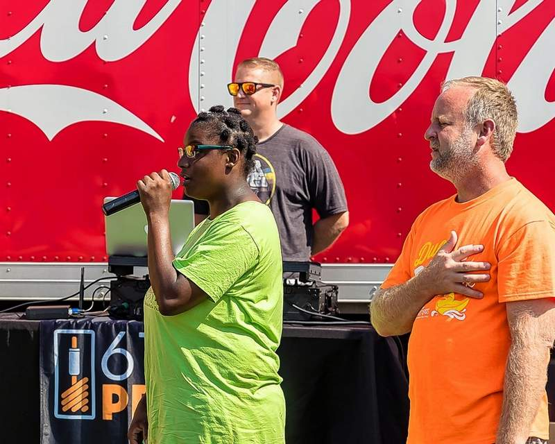 Katrina Valliant sings the National Anthem to kick off Duck Derby Dash festivities Sunday. Master of Ceremonies Keenan Rice stands alongside.
