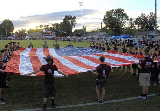Junior Rangers football players present the huge flag for the National Anthem.