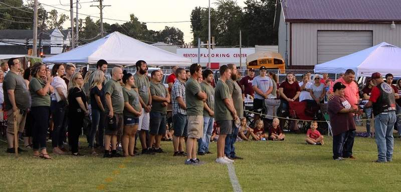 Patriot Guard members present a flag to the family of Brandon Pinson, with former Benton High School football players and 2006 graduates--the class in which Brandon Pinson graduated.