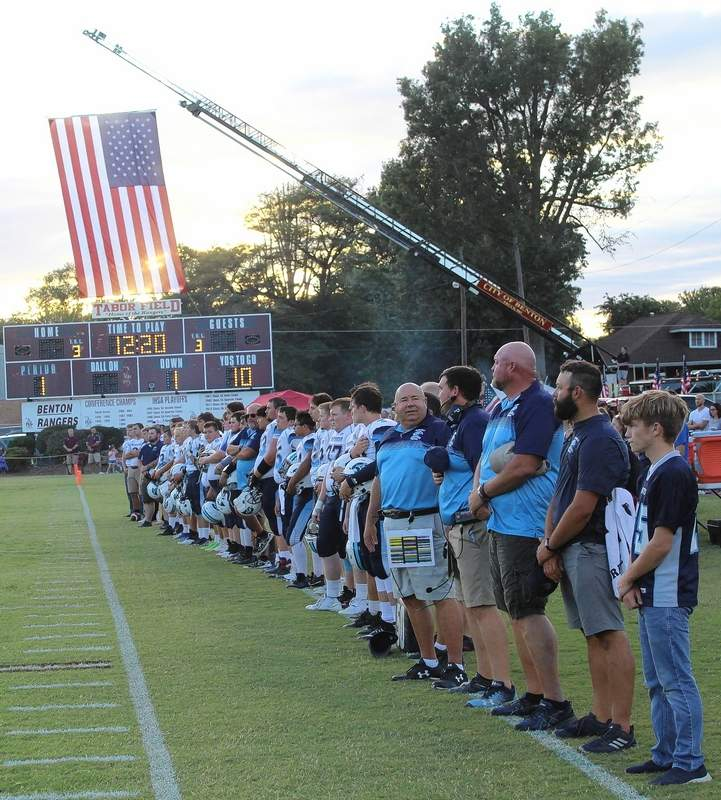 As the sun sets on the large flag presented by the Benton Fire Department, the Panthers team lines up along the sideline.