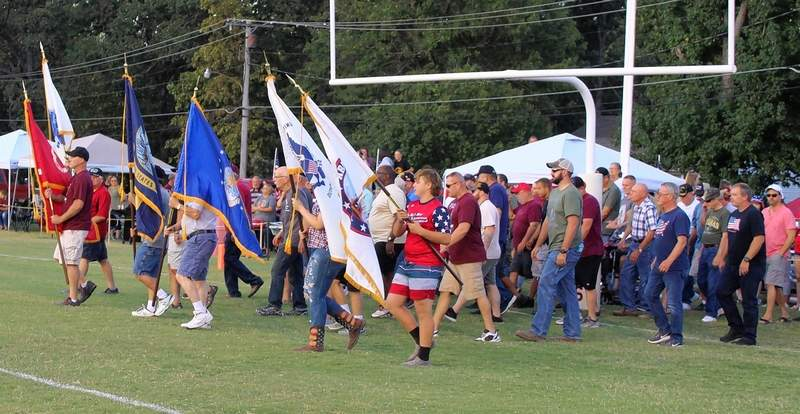 Veterans enter the field, following the flags of the various branches of the United States Armed Forces.