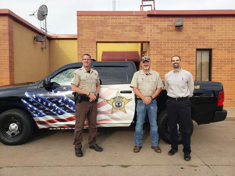 Pictured with the new patrol vehicle are USDA Area Specialist Michael McKee, Sheriff David Bartoni and Deputy Kyle Bacon.