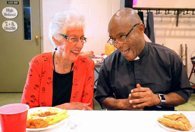 Betty Ernst of Christopher and Father Urban Osuji share a laugh while dining at the annual Fall Fish Fry St. Joseph's Catholic Church in Benton Friday night.