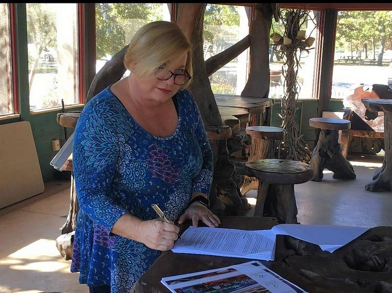 Cynde Bunch signs the casino license application.
