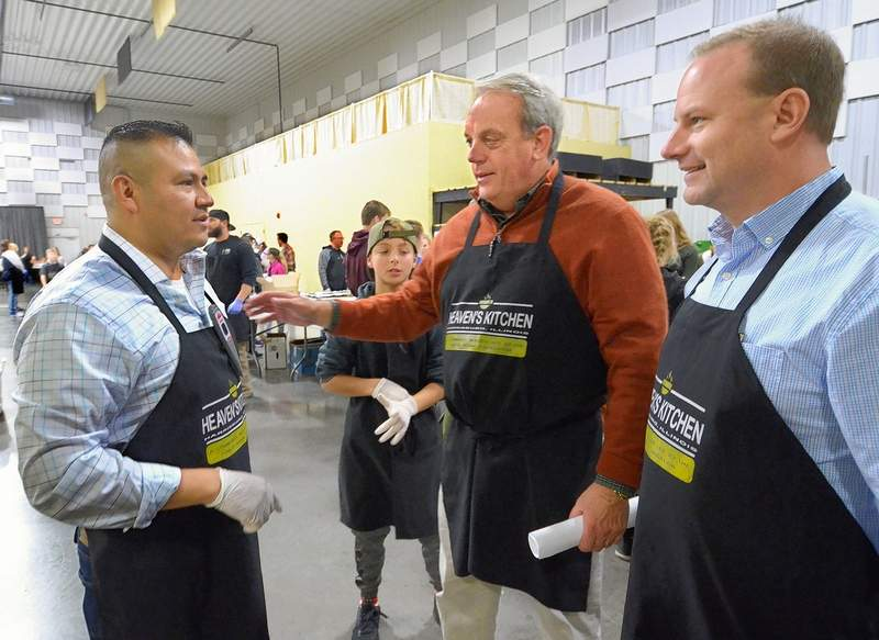 Agustin Duran, left, Sen. Dale Fowler, center, and Jeff Diederich discuss last minute plans before serving began Thursday at the first communitywide Thanksgiving dinner.