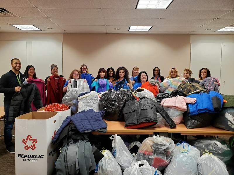 Staff members from Caritas Family Solutions prepare to sort through the 650 coats collected and donated to the agency from local Rotary clubs.