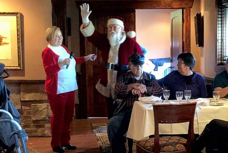Walker's Bluff owner Cynde Bunch escorts Santa to join the brunch at Legends Wednesday morning.
