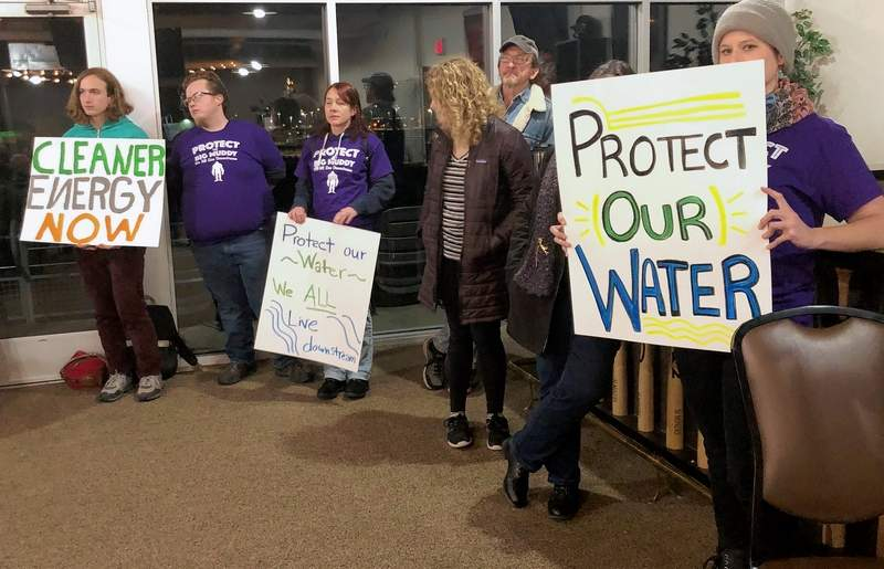 Several residents held signs to protest the dumping of wastewater from Pond Creek Mine into the Big Muddy River.