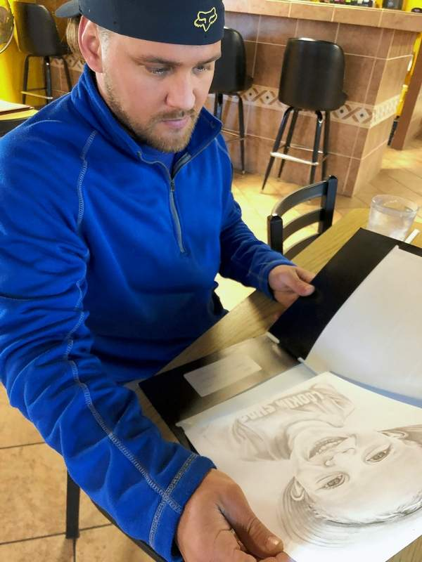 """Josh Hewlett looks at a portrait of my grandson he completed for me to give to my daughter as a birthday gift. His ability to capture """"the soul"""" of his subject in the eyes is a gift that enhances his works."""