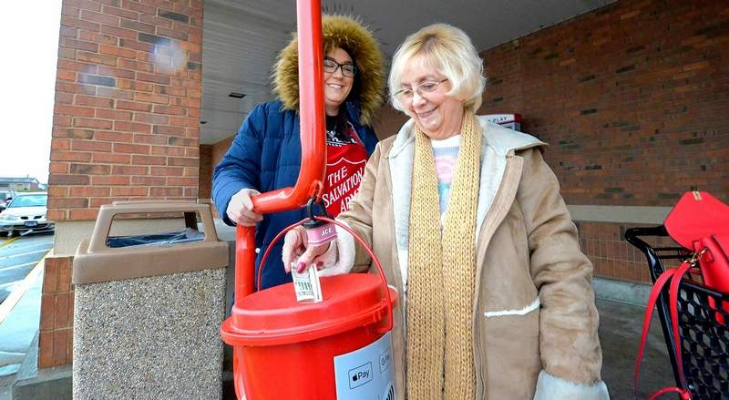 Jordon Cockrum, left, a volunteer from Banterra Bank was busy as a bell ringer at one of the familiar red kettles Friday at the Marion Kroger store. She thanked donorLinda Rendleman, right, for her contribution.