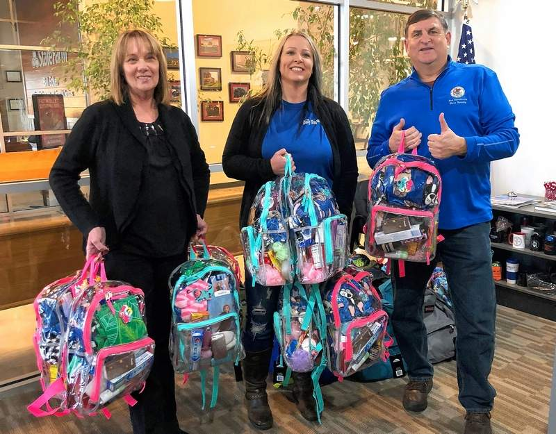 From left, Stefanie Anderson and Gatha Moore of Southern Illinois LOCAL Media Group present Rep. Dave Severin (R-Benton) with 10 filled backpacks for the Backpacks for Buddies program.