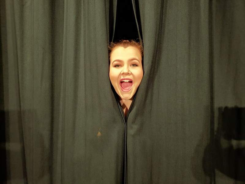 Addison Carver peeks through the backstage curtains.