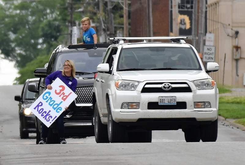East Side Intermediate third-grade teacher Stephanie Ferrell stops traffic for a quick photo with a student at the Summer Send-Off parade Tuesday.