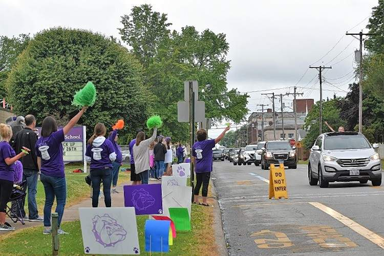 Teachers at East Side School cheer as students are driven by.