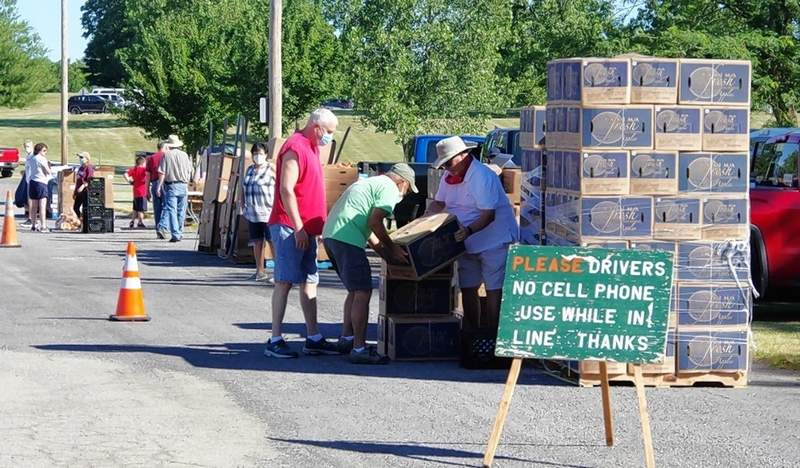 Volunteers get ready for the drive-up crowds by organizing food into four stops.