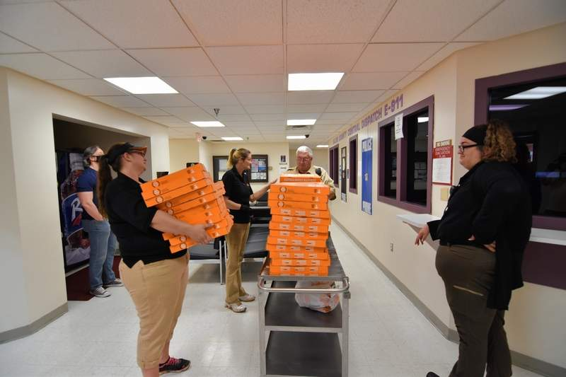 From left, Harrisburg Little Caesar's manager Darci McBrian, assistant manager Ashley Perkins, Saline County Correctional Officer Marty Wilkins and Paula Williams of Little Caesar's stack boxes of pizza to be delivered.
