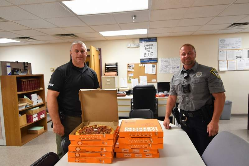 From left, Saline County Deputy Jerod Campbell and Harrisburg Police Department Officer Bobby Ragsdale prepare to have pizza for lunch.