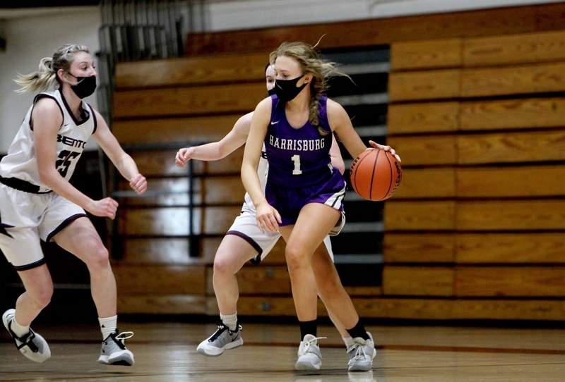 Harrisburg's Riley Harrison dribbles around the defensive pressure being applied by Benton on Friday night at Rich Herrin Gymnasium. Harrison had four points for the Bulldogs.