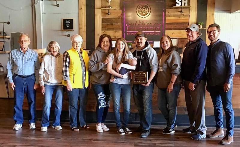 Southern Homestead By Sassafras Woodworking owners Mike and Taylor Hurt hold their Emerging Business of the Year Award, surrounded by employees and chamber members.