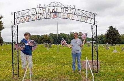 From left, Shawnee Forest NSDAR members Linda Chancey and Christy Short prepare to place flags on veterans' graves at Campground Cemetery in Ridgway.