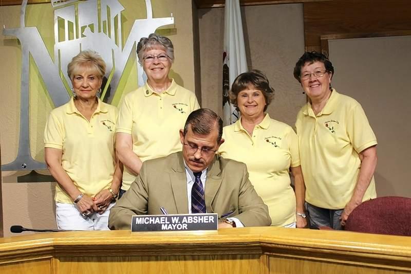 "Marion Garden Club Vice-President Sandy Long, President Debbie Lattuca, Secretary Connie Hays, and Treasurer Sheila Dingrando watch as Marion Mayor Mike Absher signs a proclamation declaring June 6-12 as ""Garden Week"" in Marion."