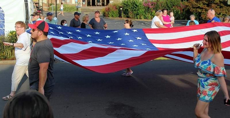 The American flag is proudly carried horizontally through the fairgrounds in the Twilight Parade.