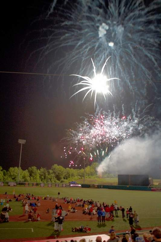 Fans climb down onto the field to get a better view of the postgame fireworks at Rent One Park.