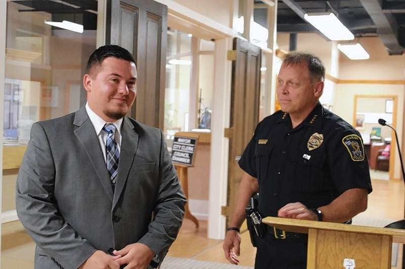 Alek Jimenez, left, is welcomed at Monday night's city council meeting by Police Chief David Fitts as a new patrol officer for the Marion Police Department. Jimenez is a former employee of The HUB and is a part-time school resource officer with the MPD. He serves as a sheriff's deputy in Pulaski County and will take up full-time patrol duties with the MPD after his swearing in later this month.